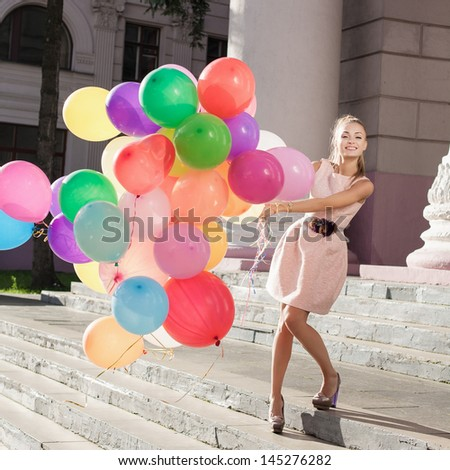 Young woman with colorful balloons, urban scene, outdoors - stock photo