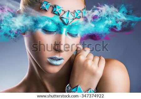Young woman with colorful green makeup with multi-colored smoke - stock photo