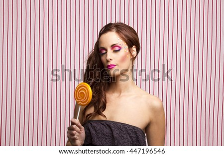 Young woman with colorful makeup and star candy glued to her face, with her eyes close holding an orange lollipop - stock photo