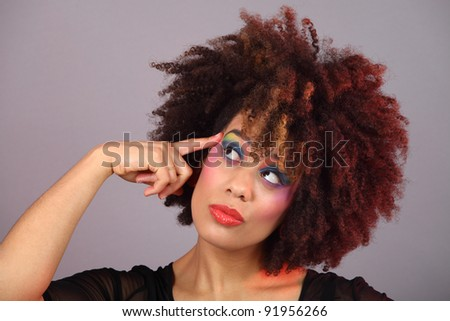 young woman with colourful make up thinking Color gels used - stock photo