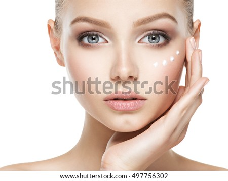 Young woman with cosmetic  cream on a clean fresh face
