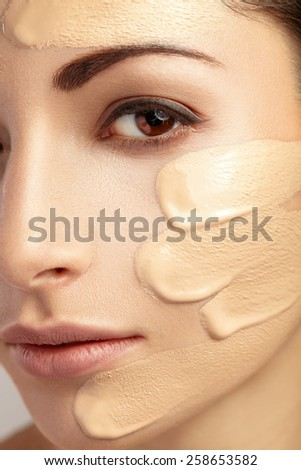 Young woman with cosmetic foundation on a skin.  - stock photo