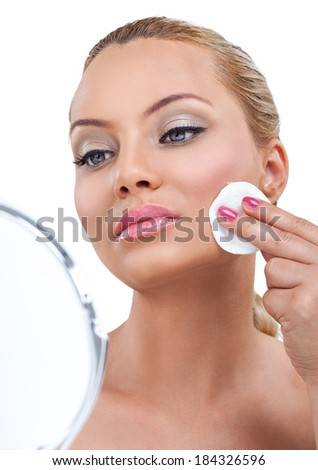 Young woman with cotton pads and mirror cleaning her skin on face - stock photo