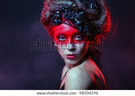 young woman with creative face-art, smoke background