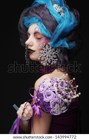 Young woman with creative make up holding a bouquet of jewelry - stock photo