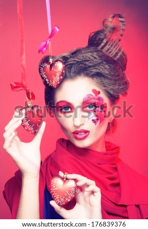 Young woman with creative make-up with red and pink hearts.