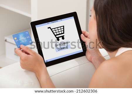 Young woman with credit card shopping online on digital tablet while lying at home - stock photo