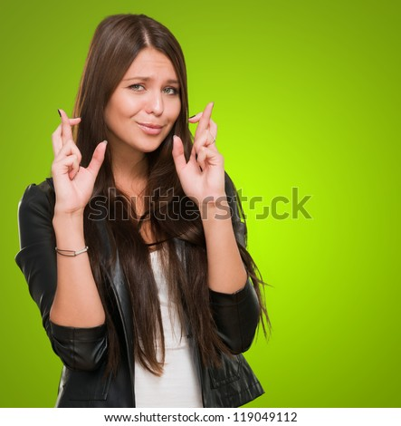Young Woman With Crossed Fingers against a green background - stock photo
