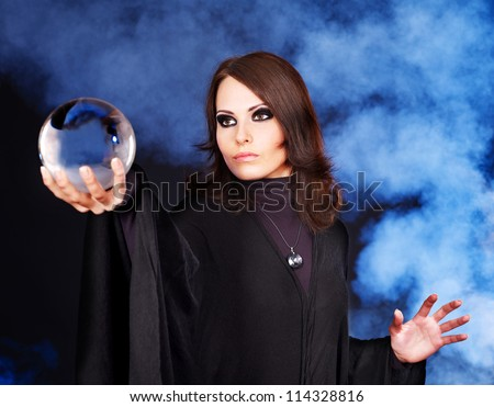 Young woman  with crystal ball. Beauty and fashion. - stock photo