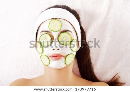 Young woman with cucumber slices on the face in a spa saloon  - stock photo