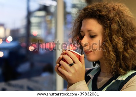 Young woman with cup of coffee in cafe at evening