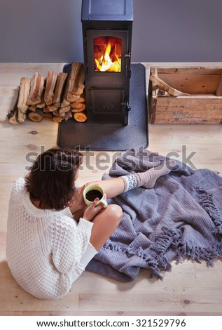 Young woman with cup of coffee sitting home by the fireplace. Fall winter relaxing and leisure concept. - stock photo