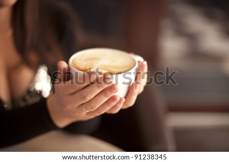 young woman with cup of hot italian coffee chocolate cappuccino in cafe restaurant - stock photo