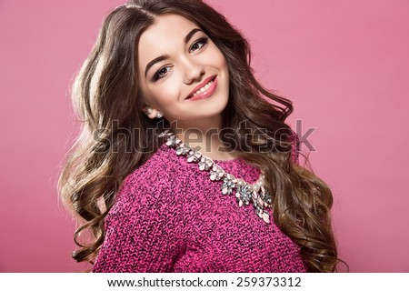 young woman with curly hair in a sweater and jeans - stock photo