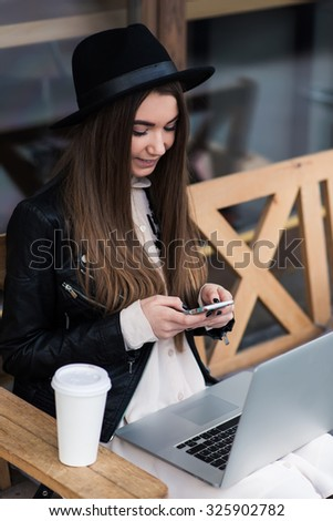 Young woman with cute smile holding on knees portable laptop computer while reading something on mobile phone, cheerful hipster girl writing text on cell telephone during work on her net-book - stock photo