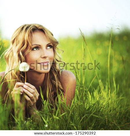 Young woman with dandelion lying on grass - stock photo