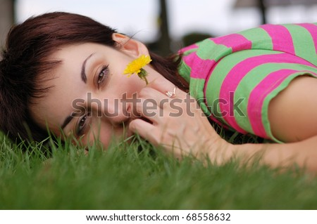 young woman with dandelion lying on green grass in spring park - stock photo
