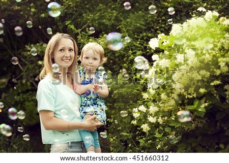 Young woman with daughter girl in her arms walks in the summer among soap bubbles - stock photo