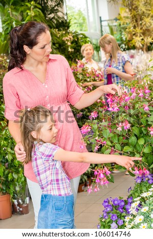 Young woman with daughter visit botanic garden shopping flowers