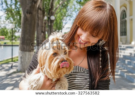 Young woman with decorative dog on hands smiling. Dog with tongue out. - stock photo