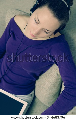 Young woman with digital tablet and headphones listening to music
