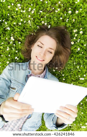 Young woman with digital tablet lying on grass and flowers