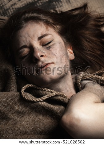 Young woman with dirty face, rope and jute cloth. Close up