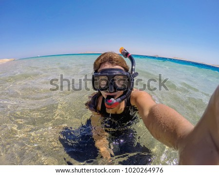 Young woman with diving mask taking a selfie in crystal water.  Sharm el Sheikh, Egypt.