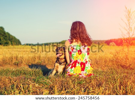 Young woman with dog in the field at sunset light back to camera - stock photo