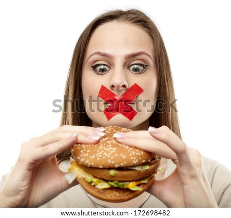 Young woman with duct tape over her mouth, preventing her to eat junk food. Healthy eating concept - stock photo