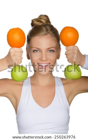 young woman with dumbbells from apples and oranges isolated on white - stock photo