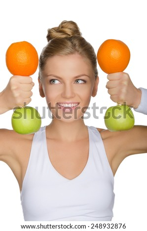 young woman with dumbbells from apples and oranges looking away isolated on white - stock photo