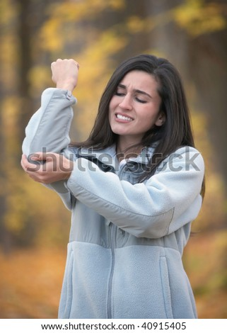Young woman with elbow pain outdoors in autumn - stock photo