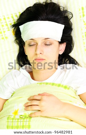 Young woman with eyes closed being ill in bed - stock photo