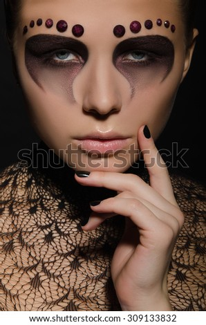 young woman with face art and decorations studio shot - stock photo