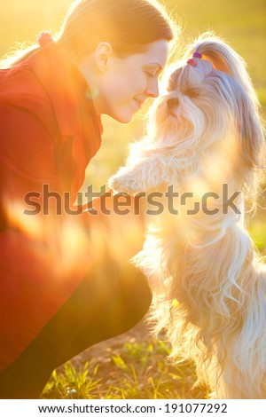 Young woman with favorite dog at sunset light. - stock photo