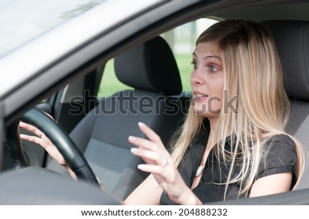 Young woman with fear in eyes driving car - hands not on steering wheel - stock photo