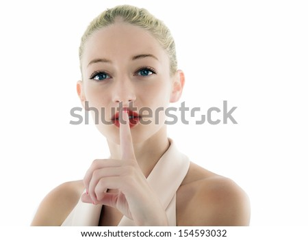 Young woman with finger on lips over white background - stock photo
