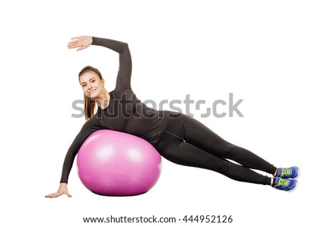 Young woman with fitness pilates ball, in black sportswear, isolated over white background. model at studio shot. Health, beauty and fitness concept.