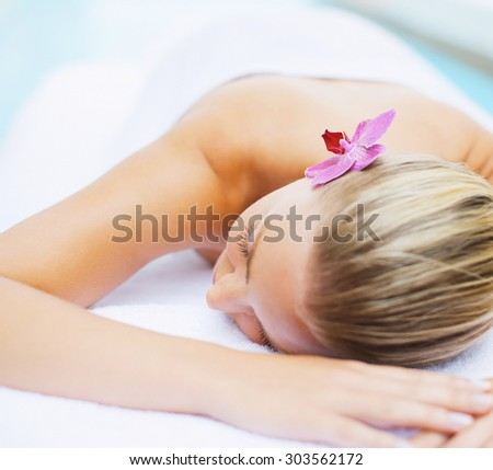 young woman with flower after spa massage - stock photo