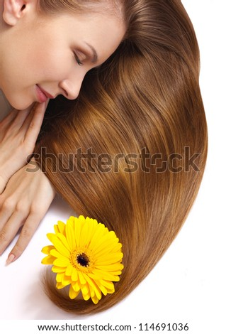 young woman with flower in long shiny hair isolated on white - stock photo