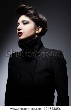 young woman with flying black hair wearing a topcoat and posing on dark background