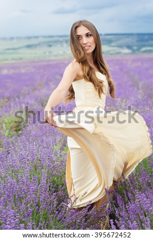 Young woman with flying hair is wearing nice white dress at field of purple lavender flowers
