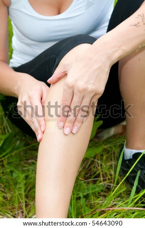 young woman with foot trauma in  field. - stock photo