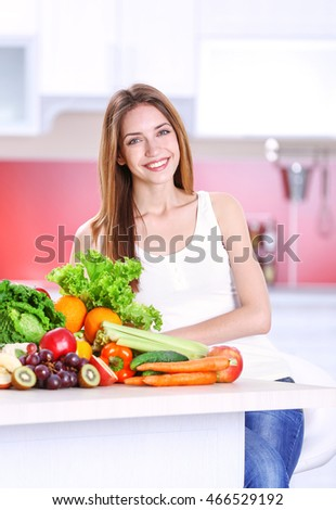 Young woman with fresh vegetables and fruits in kitchen. Diet concept