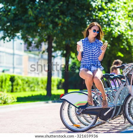 Young woman with glass of coffee on bicycle outdoor