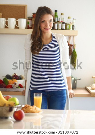 Young woman with glass of juice and cakes standing in kitchen