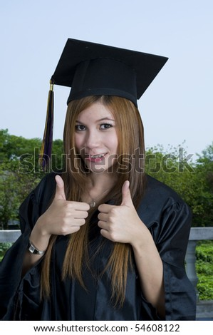 Young woman with graduation cap and gown and two thumbs up - stock photo