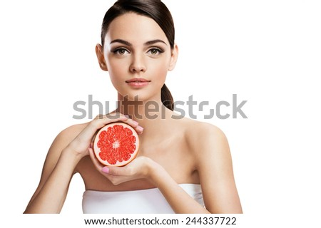 Young woman with grapefruit cut in half, healthy life concept . photo of attractive girl holding a cut piece of pomelo in her hands - isolated on white background  - stock photo