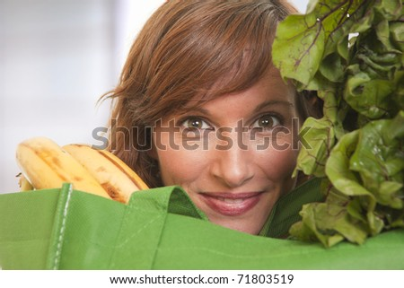 Young woman with green bag of healthy food and vegetables - stock photo